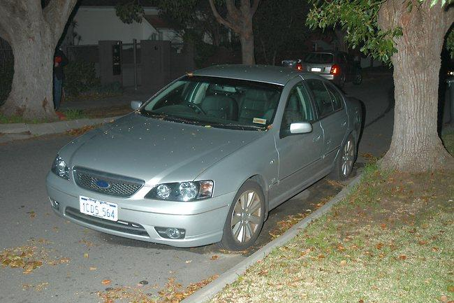 A silver-grey sedan parked in a street with large leafy trees on the verges.