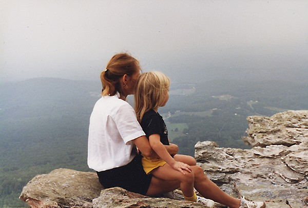 Kathleen with Caitlyn (age 5 at time of photo) in her lap, sitting on a mountaintop. They are both facing away from the camera, looking at the view.
